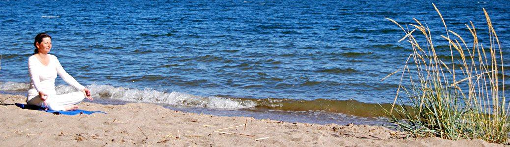 Charlotte yogar på stranden